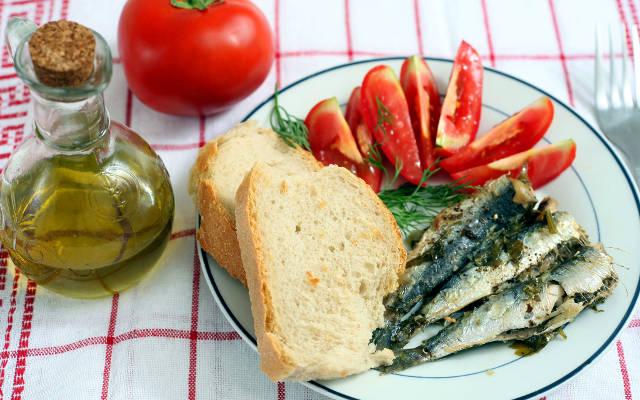 Dieta del Mediterraneo, con olio d'oliva, vino, pesce azzurro e pomodori per la salute.